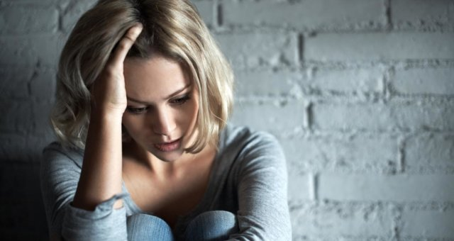 depressed-woman-sitting-against-wall-and-holding-head-in-hand