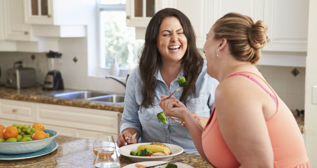 33519255 — two overweight women on diet eating healthy meal in kitchen