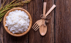 Cooking white rice (Thai Jasmine rice) in wooden bowl with wooden spoon, wooden fork and unmilled ri