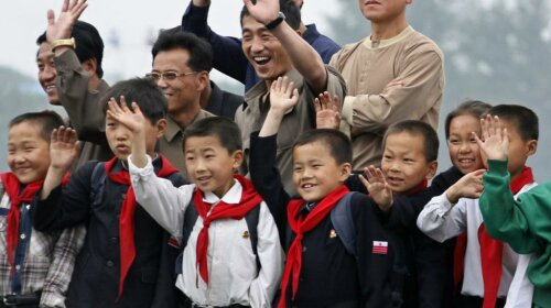 North Korean children and their parents wave to Chinese residents as they take on tour boat on Yalu