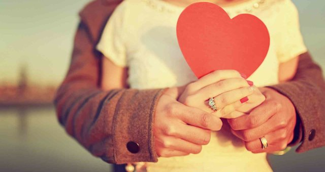 Couple-in-love-and-red-heart-in-hands