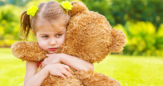 Little cute sad girl holding in hands brown teddy bear, upset ch