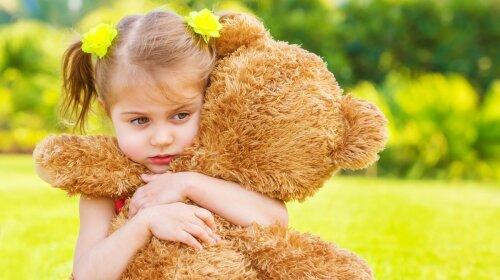 Cute Little sad girl holding hands in brown teddy bear, upset ch