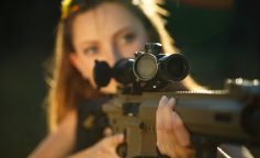 Girl with a gun for trap shooting aiming at a target