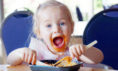 37919969 — funny little blond girl eating pasta and making a mess