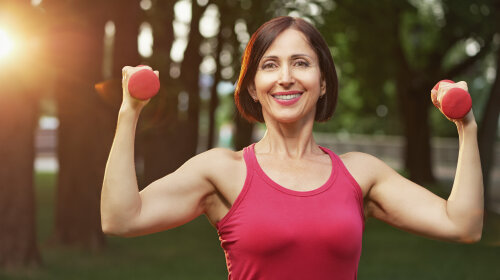 Portrait of cheerful aged woman in fitness wear exercising with