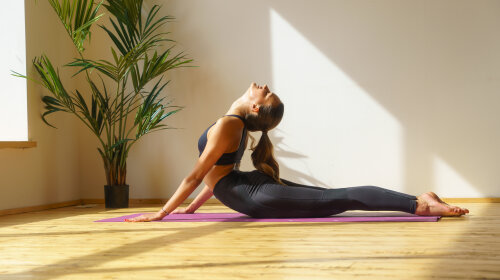 young female doing stretching yoga exercise indoot, yoga studio, natural light