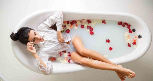 A young brunette woman takes a milk bath.