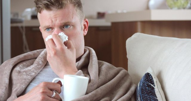 man-with-runny-nose-drinking-hot-drink-at-home-under-blanket-on-sofa