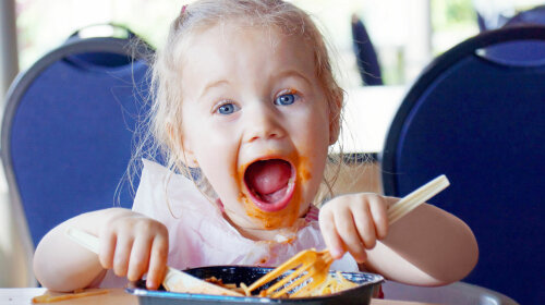 37919969 — funny little blond girl eating and pasta making a mess