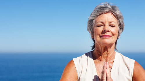 Elderly woman meditating with ocean in the background