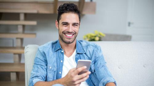 Smiling smart man using smartphone