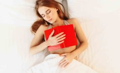 Beautiful woman with book sleeping in the bed