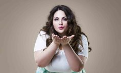 Plus size fashion model sends air kiss, fat woman on beige background, overweight female body