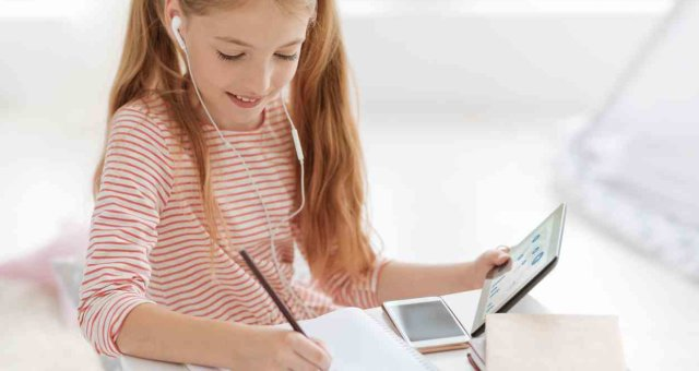 Smart schoolgirl working on home assignment