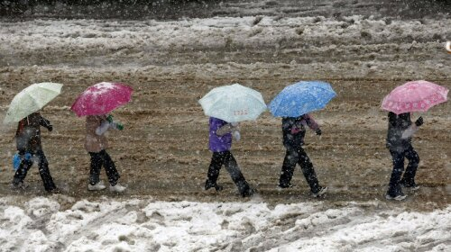 Local residents hold umbrellas as they walk on street as it snows in Shanghai