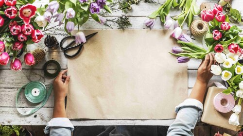 Florist Showing Empty Design Space Paper on Wooden Table with Fr