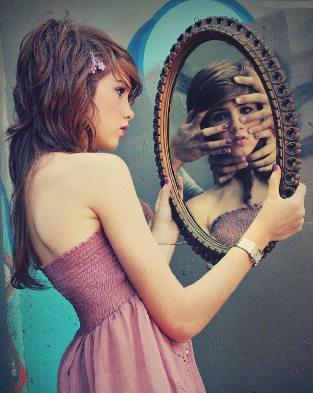 Фото как девушка смотрит на себя в зеркало